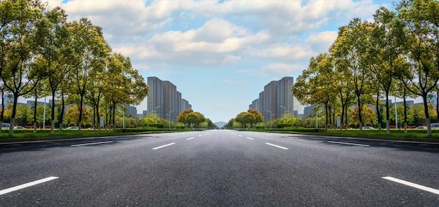 Estrada de asfalto de largura, com edifícios no horizonte