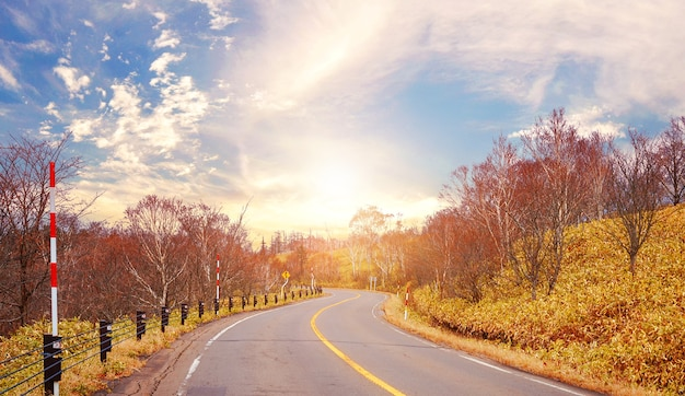 Estrada de asfalto e montanhas ao pôr do sol