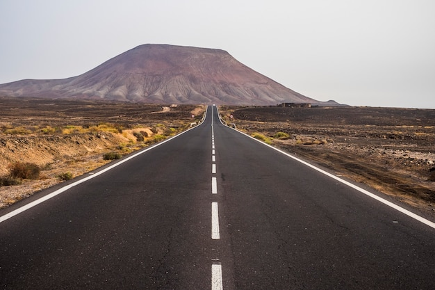 Estrada de asfalto escuro e preto no meio do deserto e dunas de areia