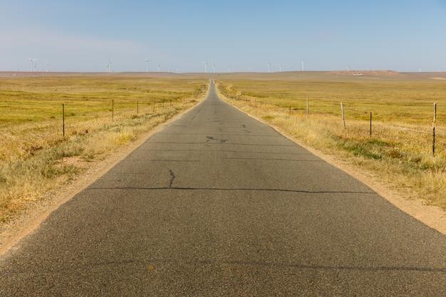Estrada de asfalto nas estepes com geradores eólicos no horizonte, interior da mongólia