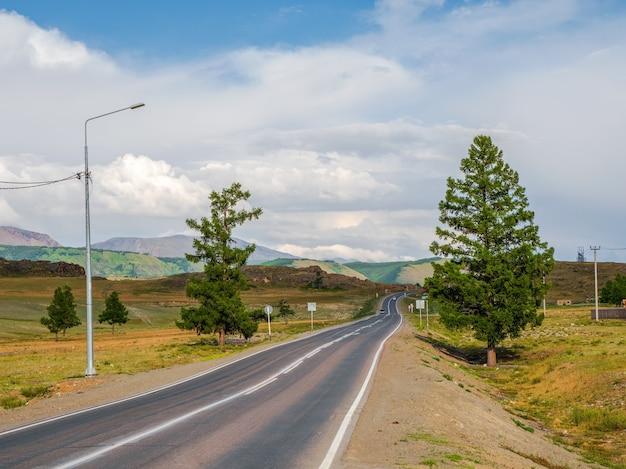 Estrada de asfalto nas montanhas de outono. trato de chuysky e uma vista da cordilheira do norte chuysky em altai, sibéria, rússia.