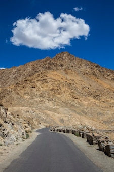 Estrada de asfalto nas montanhas do himalaia e nuvem branca no céu azul na região de ladakh, estado de jammu e caxemira, norte da índia