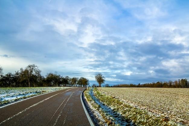 Estrada de asfalto preta vazia entre campos verdes