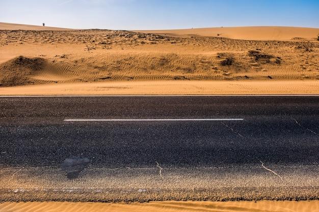 Estrada de asfalto preto com dunas de areia e deserto à esquerda e à direita e céu azul em cena