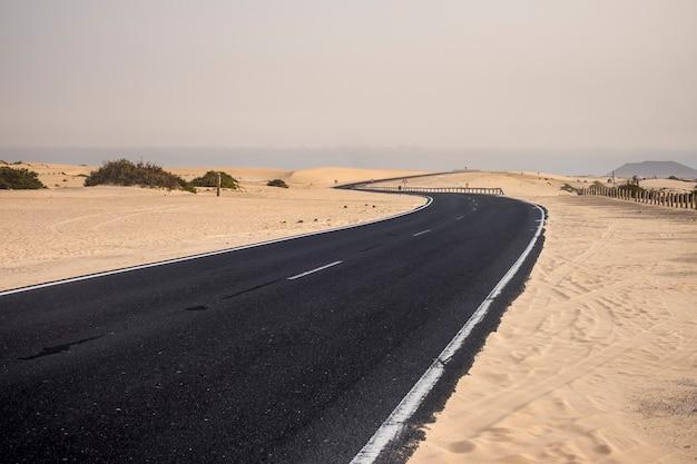 Estrada de asfalto preto no meio do deserto cruzando as dunas de areia