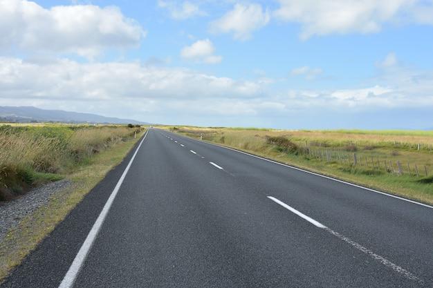 Estrada de asfalto reta em planícies hauraki