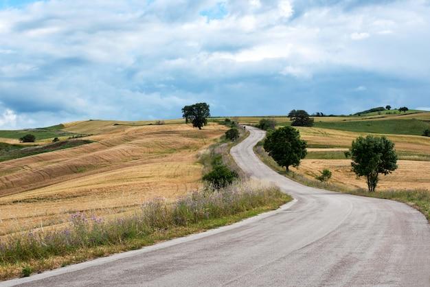 Estrada de asfalto sinuosa através de colinas