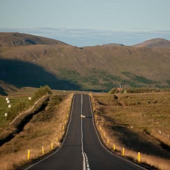 Estrada de asfalto terra rural desaparecendo no campo em direção a montanha