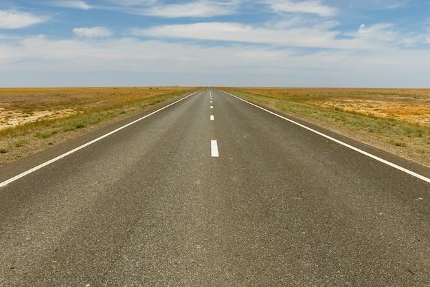 Estrada de asfalto vazia através das estepes, cazaquistão, distrito de yrgyz