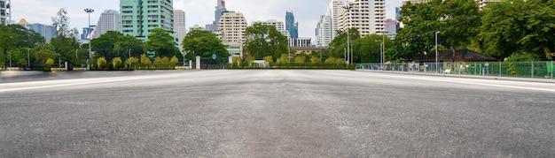 Estrada de asfalto vazia com cidade ao fundo