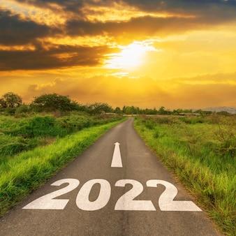 Estrada de asfalto vazia e conceito de ano novo 2022. dirigindo em uma estrada vazia para metas 2022 com o pôr do sol.