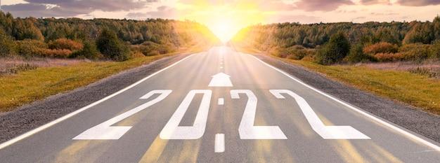 Estrada de asfalto vazia e conceito de ano novo 2022 dirigindo em uma estrada vazia para metas 2022 com o pôr do sol