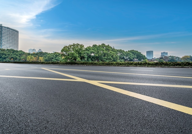 Estrada de asfalto vazia e o horizonte da cidade e a paisagem do edifício, china.