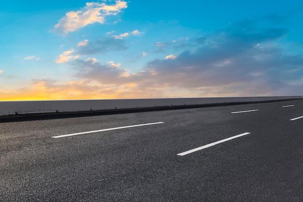 Estrada de asfalto vazia e paisagem natural no sol poente