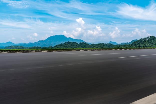 Estrada de asfalto vazia e paisagem natural sob o céu azul