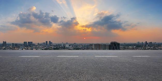 Estrada de asfalto vazia e skyline da cidade ao nascer do sol