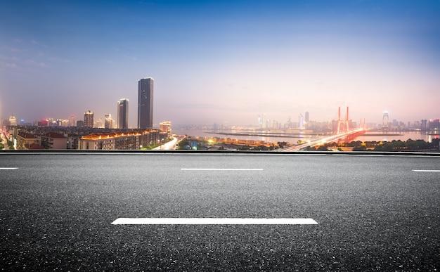 Estrada de asfalto vazia e skyline moderna à noite