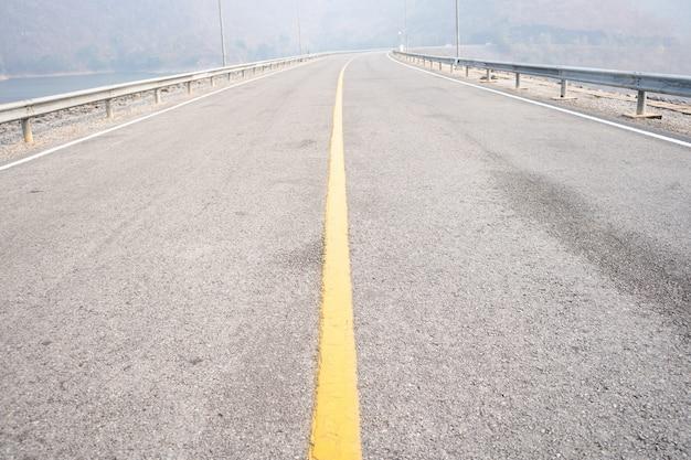 Estrada de asfalto vazia na linha média amarela de condições de neblina em dia de mau tempo cordilheira.