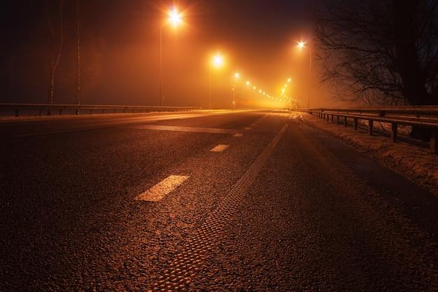 Estrada de carro vazio à noite com luzes à beira da estrada.
