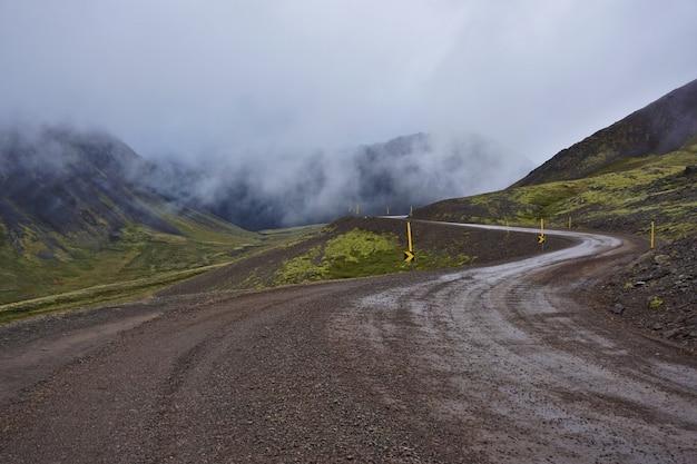 Estrada de cascalho islandesa em clima nublado islandês típico.