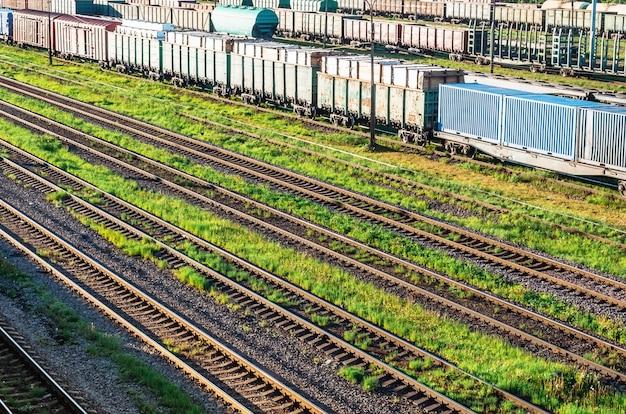 Estrada de ferro na grama do pátio de triagem, vagões de carga.