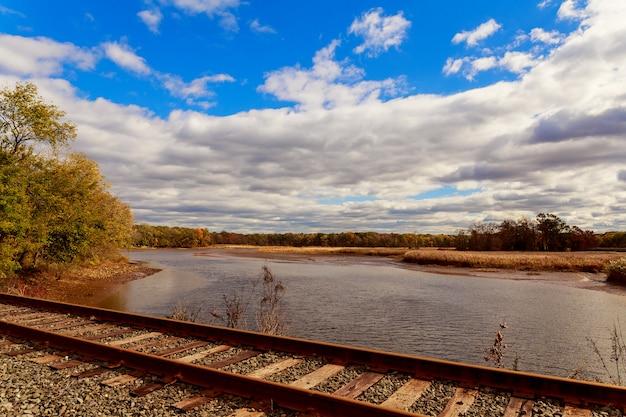 Estrada de ferro para o dia ensolarado brilhante dos trens no meio da natureza.