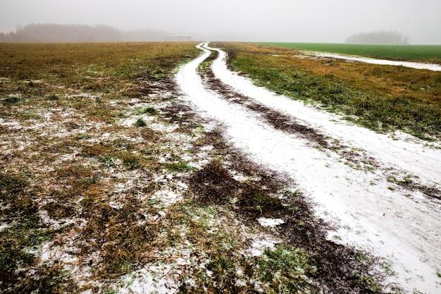 Estrada de inverno com sulcos de carros no inverno, coberta de neve após a queda de neve, sulcos de carros na estrada no campo