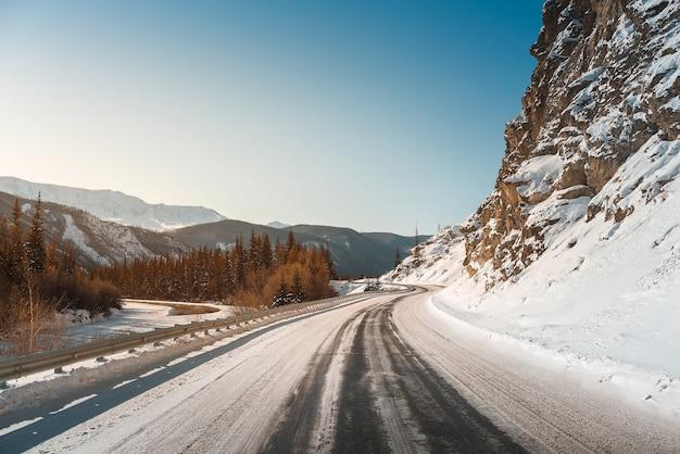 Estrada de inverno nas montanhas. pôr do sol.
