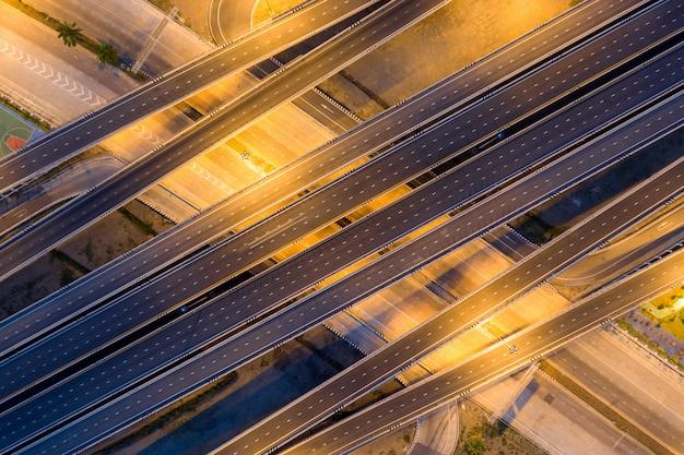 Estrada de junção de rodovia elevada multinível passando por cidade moderna em várias direções
