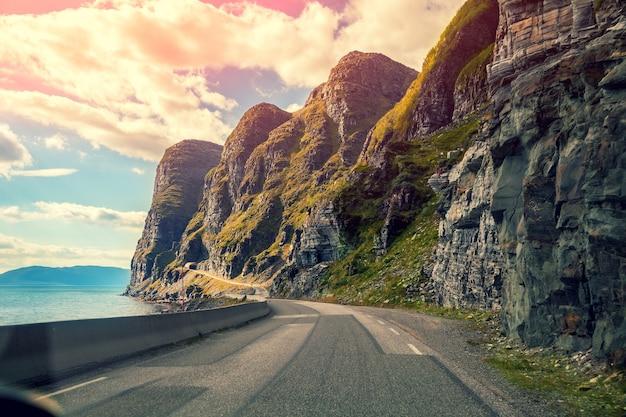 Estrada de montanha ao longo do fiorde ao pôr do sol. carro dirigindo em uma estrada de montanha