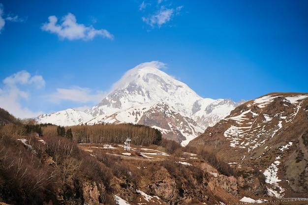 Estrada de montanha de automóveis até o sopé do monte kazbegi. cobertura de neve no topo da montanha.