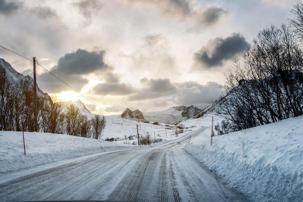Estrada de neve suja com luz do sol nas montanhas