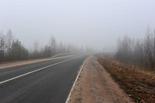 Estrada de outono no meio do nevoeiro