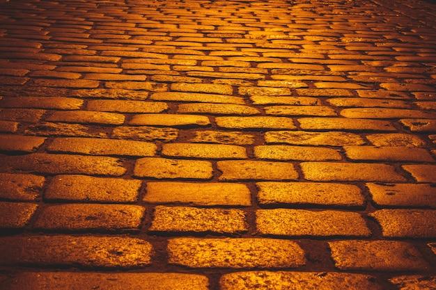 Estrada de paralelepípedos laranja com luz do sol na noite