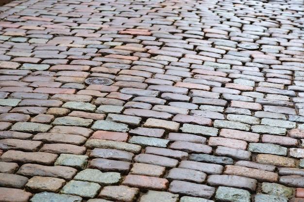 Estrada de paralelepípedos. textura de pedra fundo com pedras. foco seletivo.