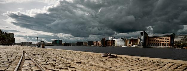 Estrada de pedra cercada por edifícios sob um céu nublado escuro