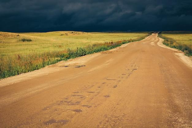 Estrada de terra à linha do horizonte sob nuvens de tempestade escuras dramáticas.