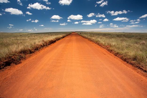 Estrada de terra laranja rural com céu azul e horizonte distante