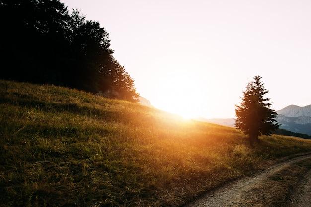 Estrada de terra leva a montanhas no pôr do sol