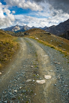 Estrada de terra na paisagem alpina cênica e céu dramático