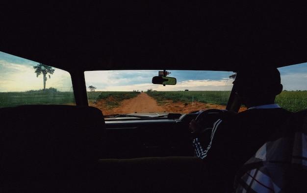 Estrada de terra no meio de campos gramados tiro de um carro com uma condução masculina