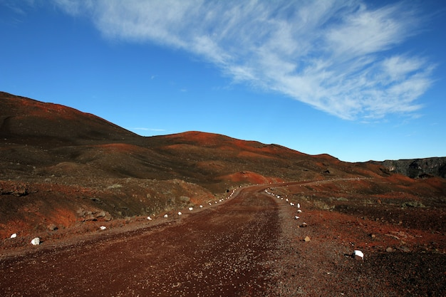 Estrada de terra no meio de colinas desertas, sob um céu azul