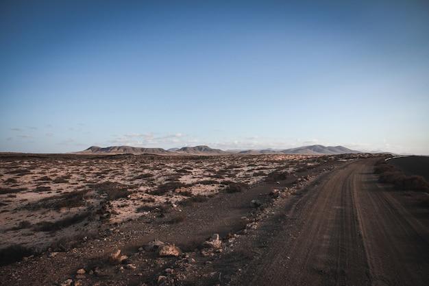 Estrada de terra perto de um campo seco com montanhas ao longe e céu azul claro