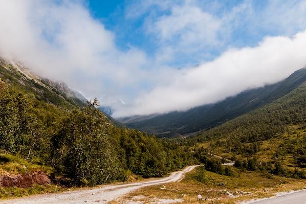 Estrada de terra reta sinuosa na paisagem de montanha verde