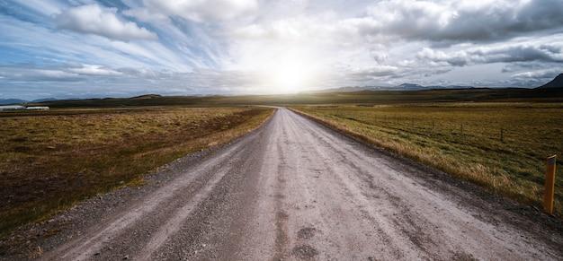 Estrada de terra vazia através da paisagem rural.