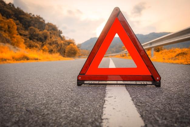 Estrada do outono triângulo vermelho, sinal vermelho de parada de emergência, símbolo vermelho de emergência na estrada.