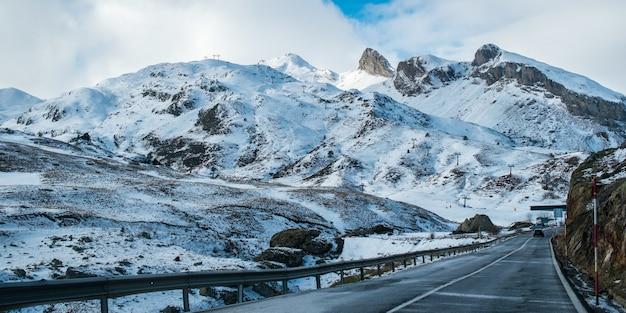Estrada estreita cercada por altas montanhas rochosas cobertas de neve sob um céu nublado