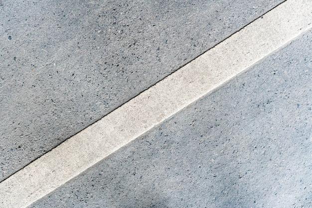 Estrada exterior com marcação de linha branca girada de 45 graus na textura inferior.