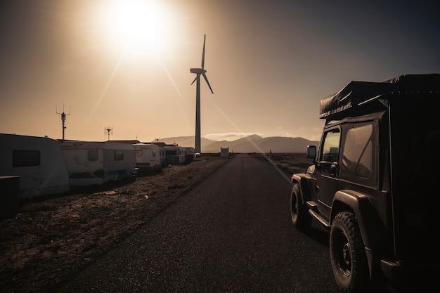Estrada longa com carro 4x4 preto off road com barraca no telhado - paisagem cênica para viagens, aventura, conceito selvagem e estilo de vida de férias diferente - sol e luz solar com céu quente
