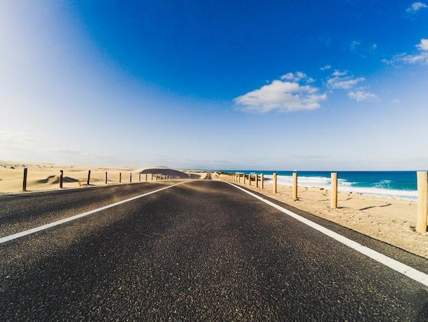 Estrada longa com deserto e praia ao lado